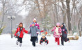Group of children and mother playing on snow in winter time adult young girl pulling sister through sled Royalty Free Stock Images