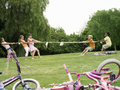 Group of children playing tug of war on grass in park profile bicycles in foreground Stock Photos
