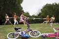 Group of children playing tug of war in park near bicycles boys versus girls side view Stock Photos
