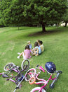 Group of children sitting on grass in park near bicycles elevated view Stock Photography