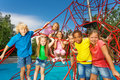 Group of children stand on red ropes and play boys girls together playground in summer Royalty Free Stock Photo