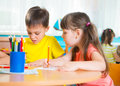 Group of cute little prescool kids drawing with colorful pencils Royalty Free Stock Photos