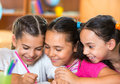 Group of cute schoolchildren having fun in classroom drawing and Stock Photos