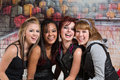 Group of cute teens laughing four diverse urban teenagers Stock Images