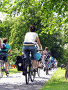 Group of cyclists in the park including some parents with their children at backseat cycles through for healthy life Royalty Free Stock Photography