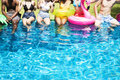 Group of diverse friends enjoying summer time by the pool with i Royalty Free Stock Photo