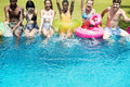 Group of diverse friends splashing water at the swimming pool Royalty Free Stock Photo
