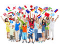 Group of diverse mixed age people celebrating large multi ethnic while holding flags Stock Images