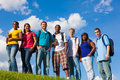 Group of diverse students friends outside a college on a hill with a sky background Royalty Free Stock Photos