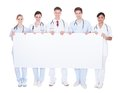 Group of doctors with blank billboard happy holding over white background Stock Image