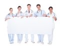 Group of doctors with blank billboard happy holding over white background Royalty Free Stock Image