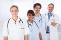 Group of doctors standing together over white happy in a row with stethoscope Royalty Free Stock Photo