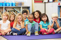 Group of elementary pupils in classroom sitting down smiling at camera Royalty Free Stock Photos