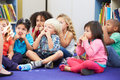 Group of elementary pupils in classroom touching noses sitting down listening to teacher Royalty Free Stock Image