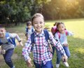 Group of elementary school kids running on the grass Royalty Free Stock Photo