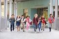 Group of elementary school kids running in a school corridor Royalty Free Stock Photo