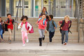 A group of elementary school kids rushing out of school Royalty Free Stock Photo