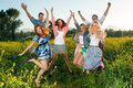 Group of excited young people leaping in the air and celebrating a beautiful hot sunny summer day as they enjoy an outing into Stock Photography