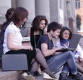Group of fellow students with books and laptop Royalty Free Stock Photo