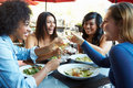 Group of female friends enjoying meal at outdoor restaurant smiling Stock Photo