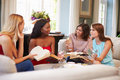Group Of Female Friends Taking Part In Book Club At Home