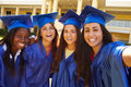 Group of female high school students celebrating graduation wearing blue cape and mortar Stock Image