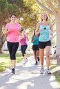 Group of female runners exercising on suburban street running towards camera Stock Photo