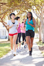 Group of female runners exercising on suburban street running towards camera Stock Images