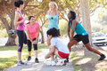 Group of female runners warming up before run smiling and Royalty Free Stock Photography