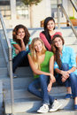 Group of female teenage pupils outside classroom sitting on steps smiling Stock Images