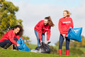 Group of female volunteers collecting litter in a feild Royalty Free Stock Photos