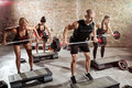 Group of fit people doing exercise with weights Royalty Free Stock Photo