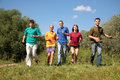 Group of five friends in multicolor  shirts runs Royalty Free Stock Photo