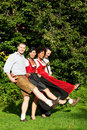 Group of four friends in Bavarian Tracht dancing Stock Photography