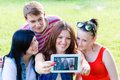 Group of four happy smilng young people friends taking picture of themselves with tablet teen on green summer outdoors background Stock Photos