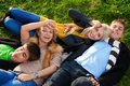 Group of four young people laying in the grass Royalty Free Stock Photo