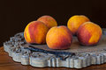 Group of fresh ripe peaches with vannilla beans on wooden decora vanilla decorative platter dark chocolate brown wallpaper Stock Photo