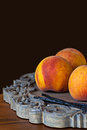 Group of fresh ripe peaches with vannilla beans on wooden platter decorative dark chocolate brown background Royalty Free Stock Images