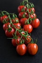 Group of fresh tomatoes on black background Royalty Free Stock Photo