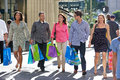 Group of friends carrying shopping bags on city street smiling Stock Photography