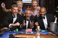 Group of friends celebrating at roulette table Royalty Free Stock Image