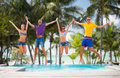 Group of friends or couples jumping on the beach summer holidays vacation happy people concept Stock Photography