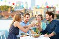Group of friends eating meal on rooftop terrace holding glass wine making a toast Stock Photo
