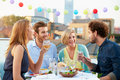 Group of friends eating meal on rooftop terrace looking at each other chatting Stock Image