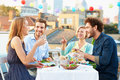 Group of friends eating meal on rooftop terrace sitting at table laughing Stock Images
