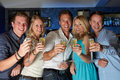 Group of friends enjoying glass of champagne in bar drink smiling to camera Royalty Free Stock Photography