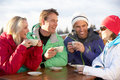 –-smiling-friends-enjoying-hot-drink-ski-resort-image107707180