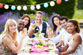 Group of friends enjoying outdoor dinner party holding glass champagne smiling to camera Stock Photo