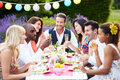 Group of friends enjoying outdoor dinner party sitting around table chatting Stock Images