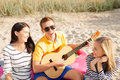 Group of friends with guitar having fun on beach summer holidays vacation music happy people concept the Royalty Free Stock Photo